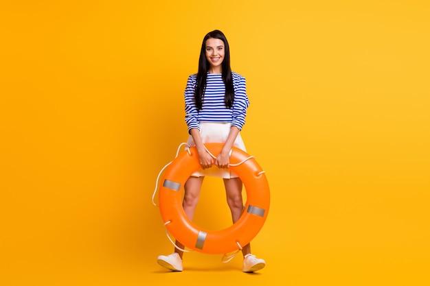 ポジティブで陽気な女の子の全身写真は、水ゴムオレンジサークル救命浮き輪を保持しますリゾートウォーターツーリズムをお楽しみください明るい輝きの色の背景の上に分離された見栄えの良い服を着てください