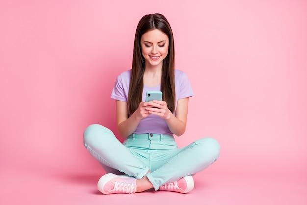 Полная длина фото позитивной жизнерадостной девушки сидит на полу, используя смартфон, делитесь репостом, подписывайтесь на новости в социальных сетях, носите бирюзовые фиолетовые фиолетовые брюки, изолированные на пастельном цветном фоне