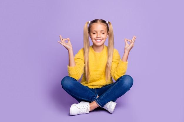 Полная длина фото позитивного жизнерадостного ребенка сидит, скрестив ноги, сложенный поезд, йога, медитация, шоу, знак ом, одежда желтого повседневного стиля, изолированная на стене фиолетового цвета