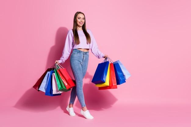 ポジティブで陽気な買い物中毒の女の子の全身写真は、多くのバッグを保持し、自由な時間をショッピングを楽しんでください50%セールウェアライラックバイオレットスタイルスタイリッシュなトレンディなジャンパー孤立したパステルカラーの背景