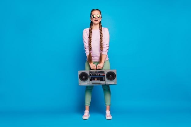 머리띠 소녀와 긍정적 인 쾌활한 젊은이의 전체 길이 사진 보류 카세트 레코드 붐 박스는 나머지에 복고풍 파티를 원하고 파란색 배경 위에 절연 분홍색 스웨터 운동화를 입고 휴식