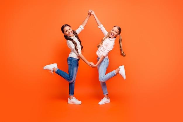 Полная длина фото позитивных сумасшедших двух детей, маленьких девочек, развлекающихся на больших осенних праздниках, держаться за руки, носить повседневную одежду, белые кроссовки, изолированные на ярком цветном фоне
