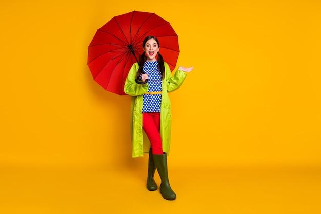 Полная длина фото позитивной девушки, наслаждающейся весенней прогулкой, держите красный зонтик, держите руку, впечатлена, без капель дождя, осенняя одежда, кеды, изолированный яркий блеск, цветной фон