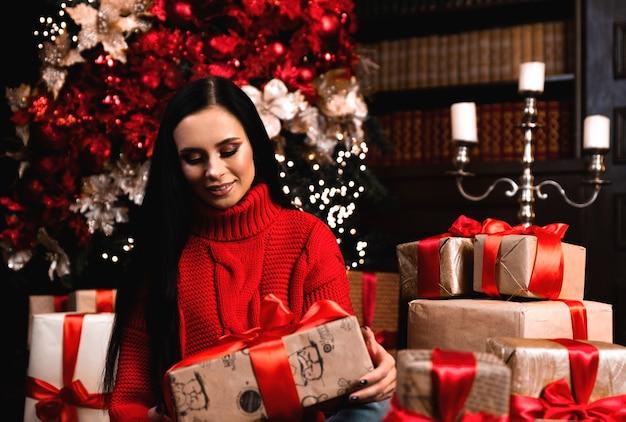 Полнометражное фото позитивной девушки в шляпе, держащей большую подарочную коробку, в рождественскую ночь, в новогодней традиции, сидя на ковре в доме.