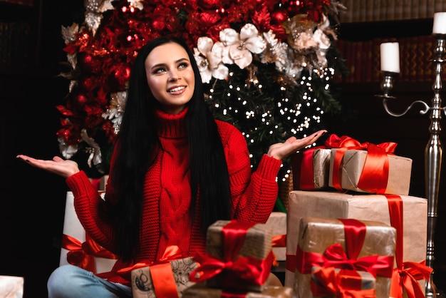 ポジティブな女の子の帽子の全身写真は大きなギフトボックスを保持しますクリスマスの夜に乗る新年の伝統を楽しむ床に座る