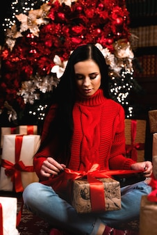 Полнометражное фото позитивной девушки в шляпе с большой подарочной коробкой в рождественскую ночь, наслаждайтесь новогодней традицией