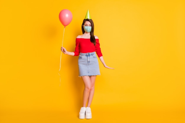医療マスクのポジティブな女の子の完全な長さの写真は、お祝いの誕生日を持っていますcovid検疫のお祝いホールドバルーンウェア赤いトップジーンズスカート脚コーン孤立した明るい輝き色の背景