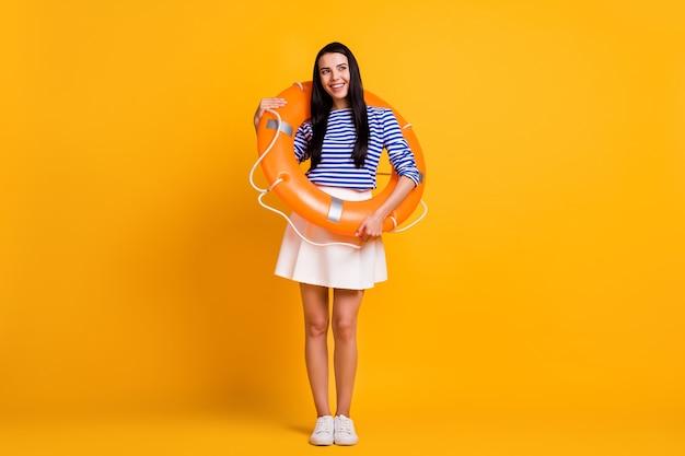 ポジティブな女の子の観光客の全身写真は、ゴム製のフロートサークルルックコピースペースドリームスイムリゾートオーシャンウェアホワイトブルーの服スニーカー分離された明るい輝きの色の背景を持っています