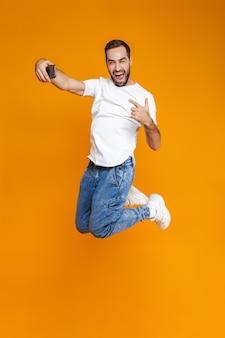 Полнометражное фото позитивного парня 30-х годов в повседневной одежде, смеющегося и делающего селфи на мобильном телефоне, изолированное