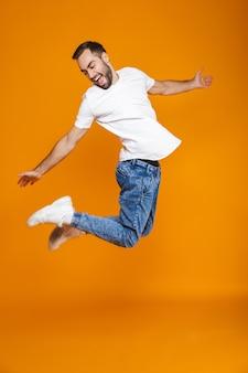 ジャンプして楽しんで、孤立したtシャツとジーンズのポジティブな男の全身写真
