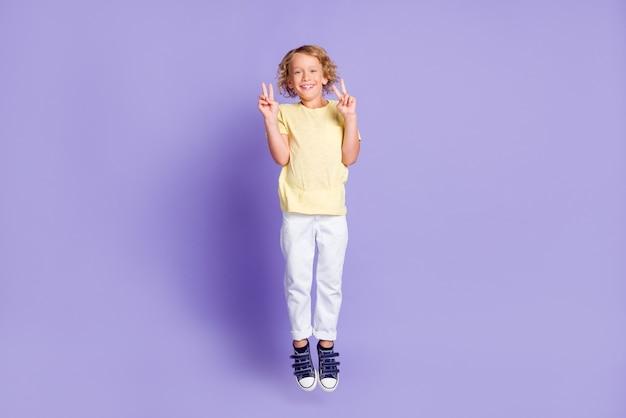 Полная длина фото позитивного маленького мальчика, подпрыгивающего, заставляет v-знак носить белую желтую футболку, изолированную на фиолетовом фоне