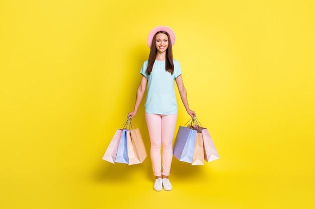 Полная фотография позитивной туристической девушки, заканчивающей свой отдых, расслабьтесь, курорт, купите семейные сувениры, проведите много сумок, наденьте сине-розовую обувь, изолированную на ярком блестящем цветном фоне