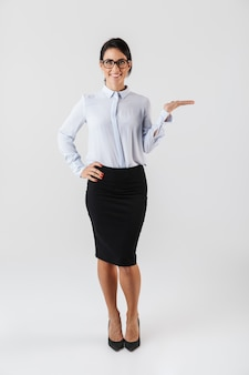 흰 벽에 고립 된 사무실에 서있는 안경을 쓰고 예쁜 사업가의 전체 길이 사진