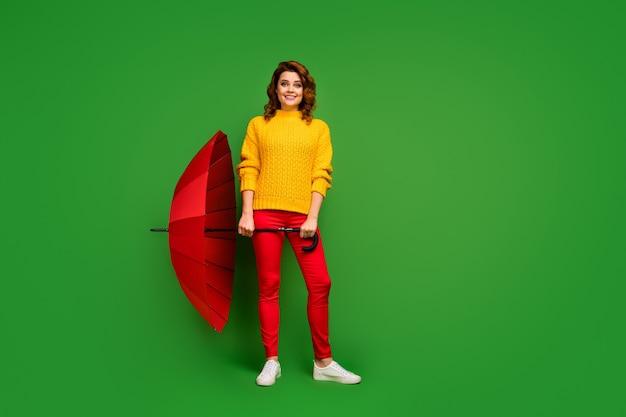 Фотография в полный рост довольно жизнерадостной женщины, держащей большой яркий зонтик, прогулка в дождливый теплый весенний день, погода, желтый свитер, красные брюки, обувь, изолированные на стене зеленого цвета