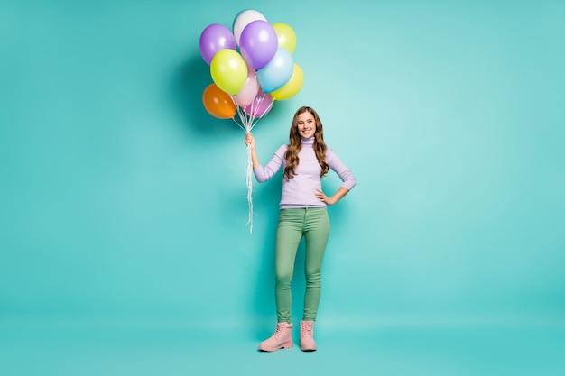 かなりファンキーな女性の全身写真は、親友のためのサプライズパーティーをアレンジする多くのカラフルな気球を運びますライラックジャンパーグリーンパンツブーツ孤立したパステルティールカラー