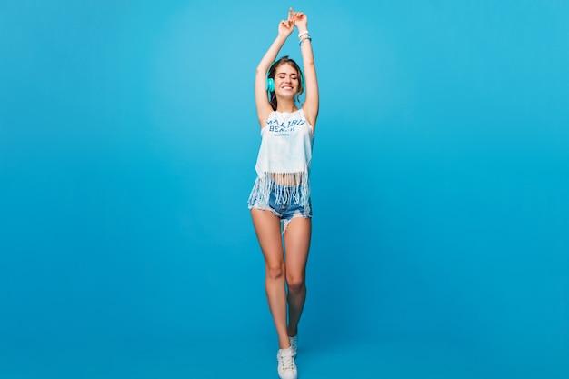 Фото в полный рост красивой девушки с длинными вьющимися волосами на синем фоне в студии. она носит белую футболку, шорты. она слушает музыку в синих наушниках и выглядит довольной.