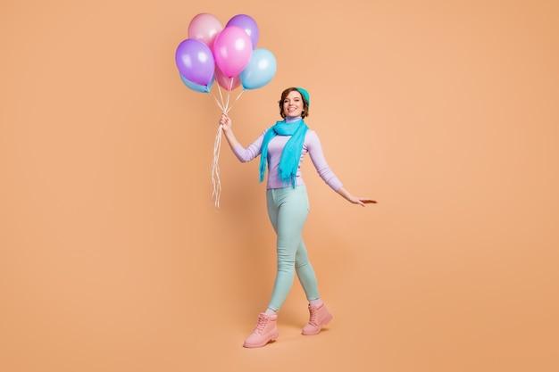 예쁜 숙녀의 전체 길이 사진은 깜짝 파티를 걷는 많은 공기 풍선을 들고 가장 친한 친구가 라일락 보라색 점퍼 녹색 바지 부츠 파란색 베레모 스카프 격리 된 베이지 색 배경을 착용합니다.
