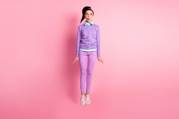 きれいな女性のジャンプの完全な長さの写真驚いた着用メガネバイオレットジャンパーパンツスニーカー孤立したピンク色の背景