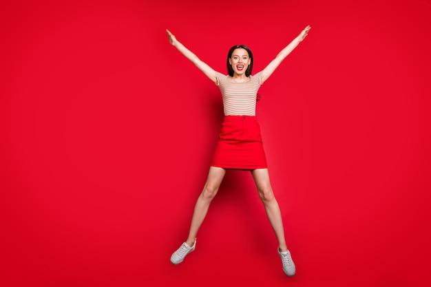 예쁜 아가씨의 전체 길이 사진은 별 모양으로 높이 점프 프리미엄 사진