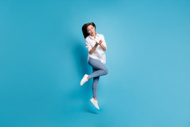 Полная длина фото красивой леди прыгает высоко, отправляя воздушные поцелуи, носить белую рубашку, джинсовую обувь, изолированный синий цвет фона