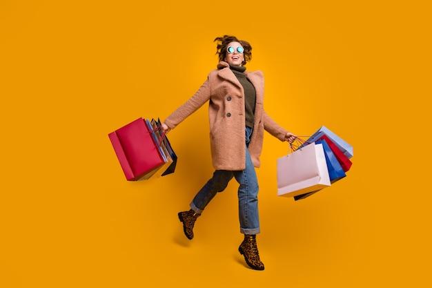 예쁜 아가씨 점프 산책 쇼핑 센터의 전체 길이 사진은 많은 팩을 착용 캐주얼 핑크 코트 풀오버 청바지 레오파드 프린트 신발을 착용