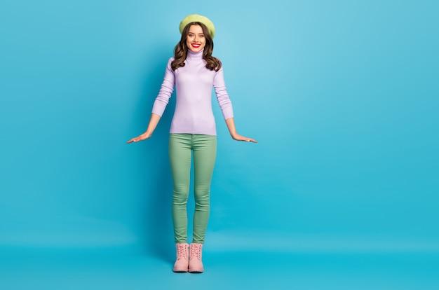 Фото в полный рост симпатичной дамы стильный внешний вид хорошее настроение прогулка уличная одежда современный зеленый берет шляпа фиолетовая водолазка джемпер брюки туфли изолированные стена синего цвета