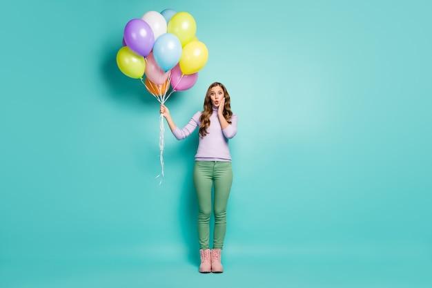かなりショックを受けた女性の全身写真は、多くのカラフルな気球を運びます予期しないサプライズパーティーウェアライラックジャンパーグリーンパンツブーツ孤立したティールパステルカラー