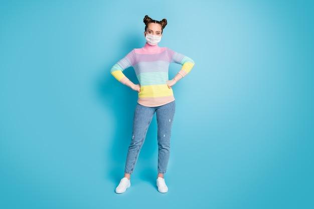 예쁜 10대 여성의 전체 길이 사진은 외부에서 사회적 거리를 유지하며 신선한 공기를 마시며 슈퍼마켓에서 얼굴 마스크를 보호하는 청바지 줄무늬 풀오버 신발을 격리된 파란색 배경
