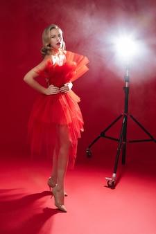 빨간 배경에 스튜디오에서 포즈를 취하는 디자이너 빨간 드레스를 입은 예쁜 젊은 여성의 전체 길이 사진. 세인트 발렌타인 데이 개념