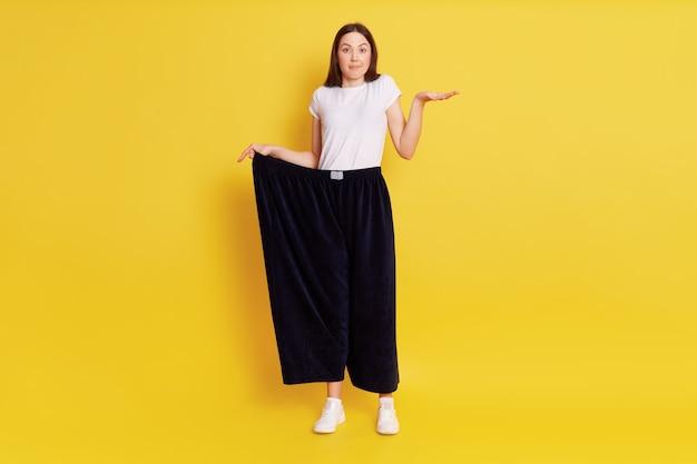 너무 큰 블래 그 바지를 입고, 손바닥을 옆으로 뻗고, 카메라를보고, 너무 많은 무게를 잃고 놀란 놀란 놀란 여성의 전체 길이 사진, 노란색 벽 위에 고립 된 포즈.