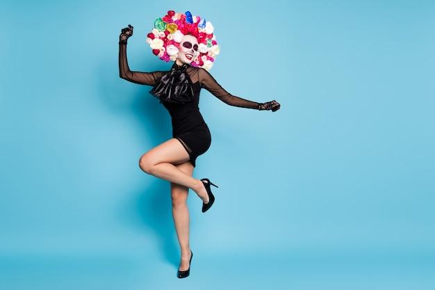 Полная фотография страшного существа, женского танцевального конкурса, латинского тематического мероприятия, носить черное кружево, короткое мини-платье, перчатки на высоких каблуках, костюм смерти, розы, повязка на голову, изолированный синий цвет фона