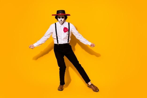 Полная фотография страшного пугающего парня-монстра танцует притвориться тореадором, сражающимся с быком, носить белую рубашку, костюм смерти розы, сахарный череп, подтяжки сомбреро, изолированный желтый цвет фона