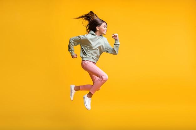Полная длина фото школьников в воздухе, летающих прыжки руки кулак, изолированные на фоне желтого цвета