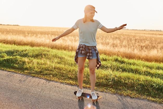 日没のアスファルト道路でカジュアルな服とヘアバンドスケートボードを着て、腕を上げて、アクティブな娯楽を楽しんでいるスリムな美しい女性の全身写真。