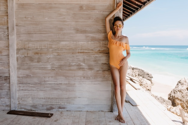 Фото в полный рост стройной задумчивой девушки, стоящей со скрещенными ногами возле деревянного дома. открытый выстрел женщины брюнетки в элегантных оранжевых купальниках, охлаждая на экзотическом курорте.