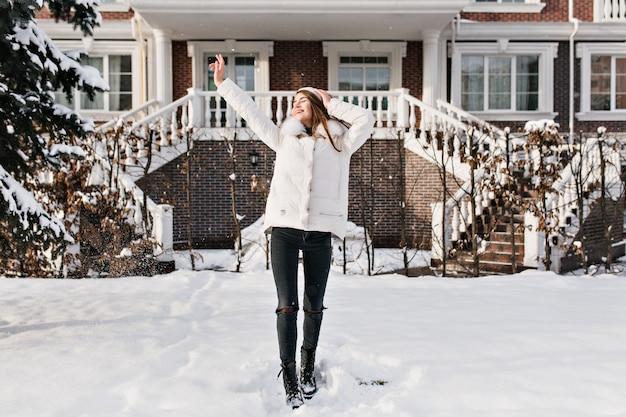 冬の週末を楽しんでいる暖かいスタイリッシュな服を着たスリムな若い女性の全身写真。寒い日に手を挙げろ暗いズボンで魅力的な白人女性の屋外のポートレート。