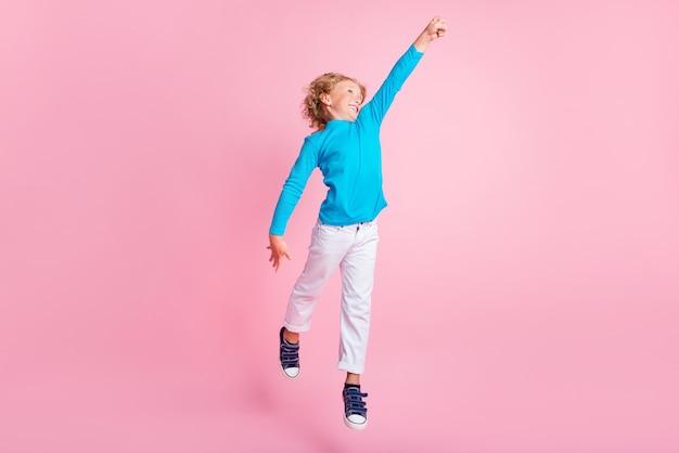 Полная длина фото маленького мальчика прыгать, поднимать кулак, носить синие водолазки, кроссовки, изолировать пастельно-розовый цвет фона