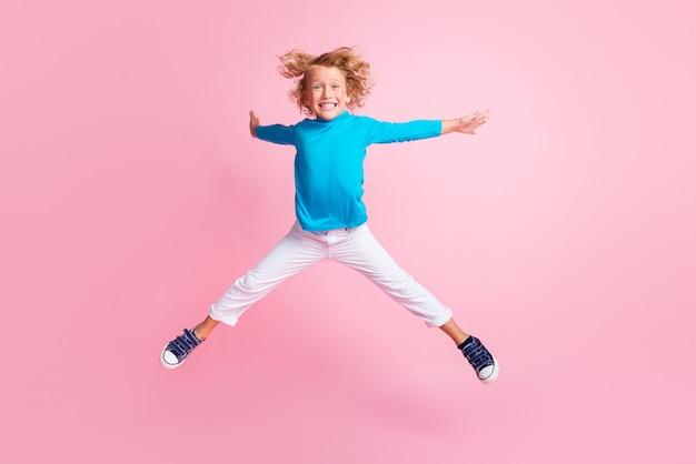 작은 아이 점프 다리 손 스타의 전체 길이 사진은 파란색 터틀넥 바지 운동화를 입고 파스텔 핑크색 배경에 고립