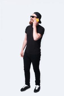 Полная длина фото улыбающегося бородатый мужчина разговаривает по смартфону