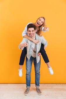 Полная длина фото улыбающейся пары, развлекающейся и указывающей на вас пальцами, в то время как мужчина сидит на спине счастливой женщины