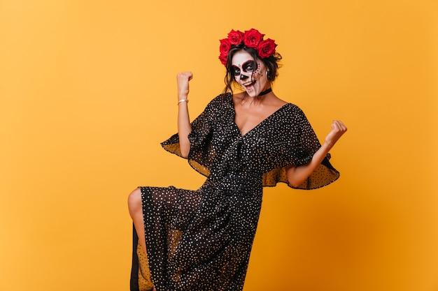 승리 제스처를 만드는 웃는 소녀의 전신 사진. 검은 쉬폰 드레스에 레이디 할로윈 마스크와 함께 포즈.