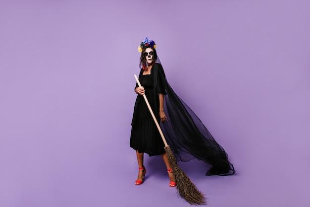 검은 색 차가운 복장에 해골 마스크가있는 마법사의 전체 길이 사진. 라일락 벽에 빗자루와 함께 포즈를 취하는 여자.