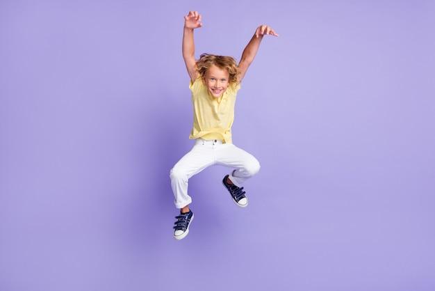 Полная длина фото жуткого маленького мальчика в прыжке с атакой руками когтями в футболке с брюками, изолированными на фиолетовом цветном фоне