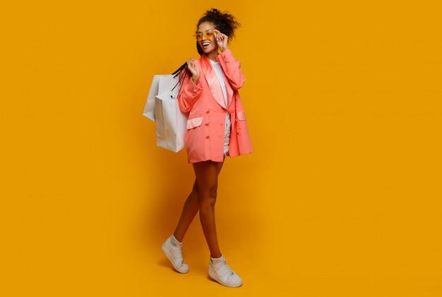 黄色の背景の上に買い物袋を持って立っている白いスニーカーで黒い肌を持つスタイリッシュなアメリカ人の女の子の完全な長さの写真。