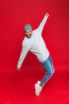 캐주얼에 세련된 남자 30 대 미소와 격리 점프의 전체 길이 사진 프리미엄 사진