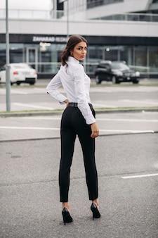黒のズボンと白いシャツを着て、モダンな建物の向かいに立っているスタイリッシュな女性の全身写真。スタイルとファッションのコンセプト