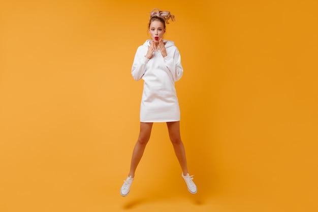 Полное фото удивленной женщины с волосами в хвосте, прыгающей в оранжевой комнате