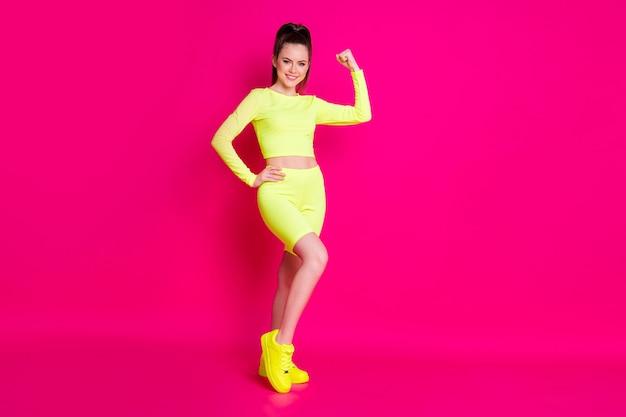 Полная длина фото сладкой очаровательной спортивной девушки, одетой в желтый наряд, показывающая мышцы, поднимающие кулак, изолированный розовый цвет фона