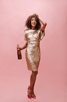 반짝이 드레스와 웃 고 분홍색 벽에 음료 병을 들고 빨간 발 뒤꿈치에 갈색 곱슬 머리를 가진 유행 여자의 전체 길이 사진 ..