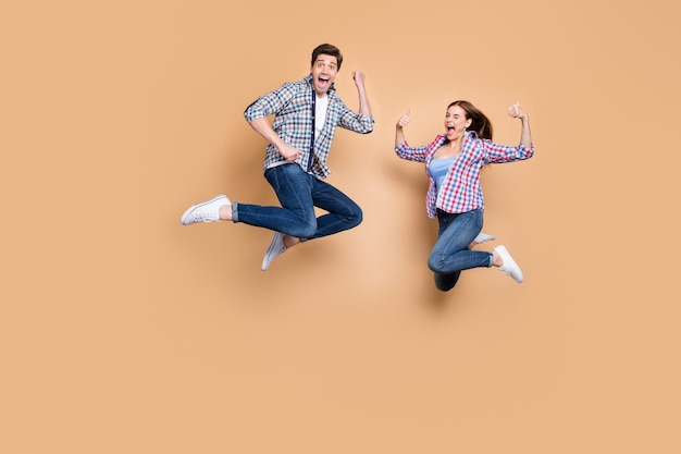 Полная длина фото двух человек сумасшедшая леди парень прыгает высоко поднимая палец вверх празднует успешную победу носить повседневную клетчатую джинсовую одежду изолирован на бежевом цветном фоне